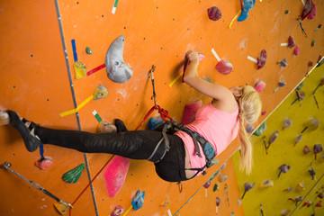 young girl climbs the steep wall on climbing gym