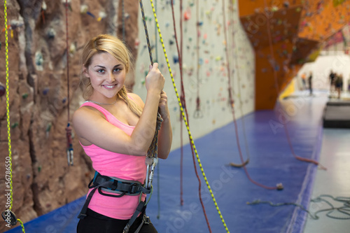 smiling girl holds on to the rope on climbing gym