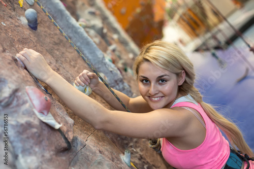 Smiling girl with climbing equipment hanging on wall