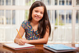 Cute Hispanic little girl studying at home and smiling