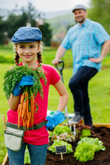 Harvests - girl helping father in vegetable garden