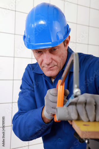 Manual worker cutting length of pipe