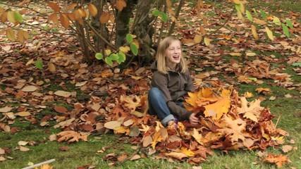 Girl raking fall leaves