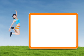 Fitness woman jumping next to copyspace