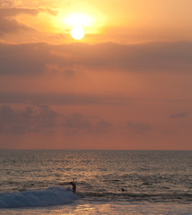 Surfer at sunset in Ocean Wave in Bali, Indonesia