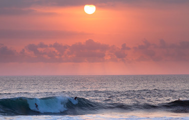 Surfer riding at sunset in Ocean Wave in Bali, Indonesia