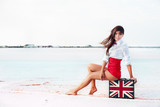 Beautiful young woman with suitcase with British flag outdoor