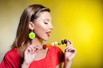 Beautiful young woman with fruit skewer