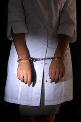 Doctor in handcuffs on dark background
