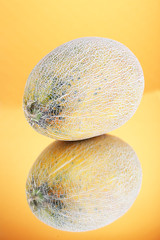 Ripe melon on orange background