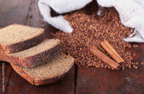 Cloth bag with buckwheat and bread on wooden background