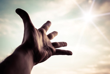 Hand of a man reaching to towards sky. Color toned image.