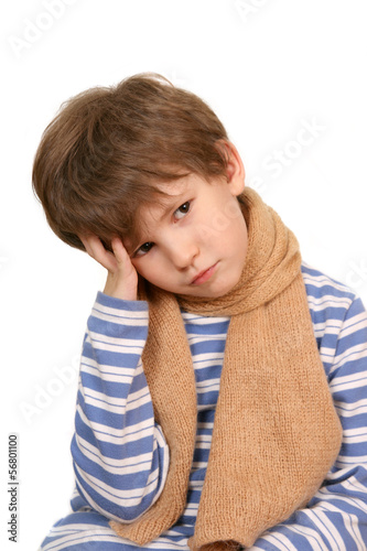 The sad boy with a scarf holds the head