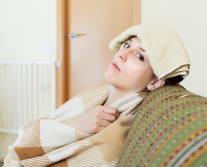 woman having headache holding towel