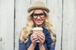 Cheerful fashionable blonde holding coffee outdoors