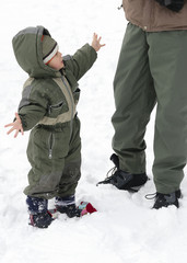 Child in winter snow with parent