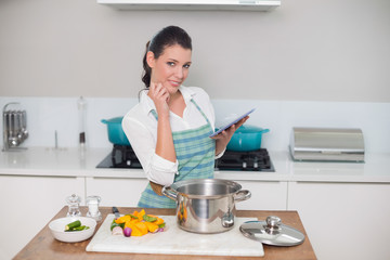 Happy gorgeous woman wearing apron using tablet
