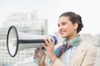 Pleased smart brown haired businesswoman holding a megaphone