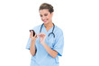 Content brown haired nurse in blue scrubs using a mobile phone