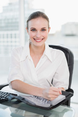 Businesswoman writing in her diary smiling at camera