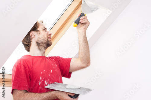 Manual worker with wall plastering tools inside a house