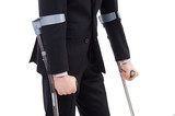 Businessman in a suit holding crutches