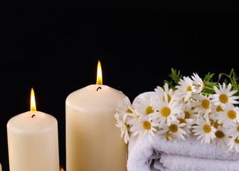 aromatherapy with candles with on towel and flower