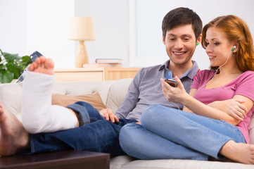 Yuong couple sitting on sofa and listening to the music