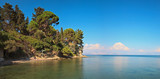 Panoramic long exposure shot of blue sea with blue cloudy sky on