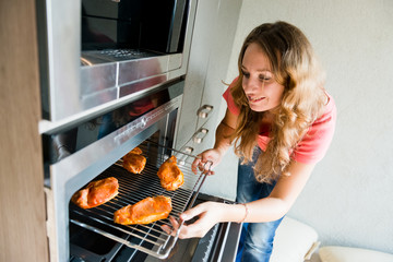 woman putting meat into oven