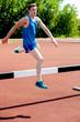 Male athlete jumping hurdle