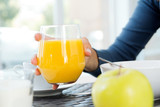 woman's hand grabbing a glass of orange juice at breakfast