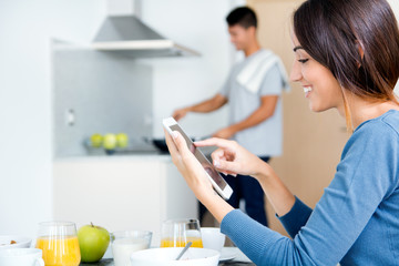 couple in the kitchen preparing breakfast and browsing  internet