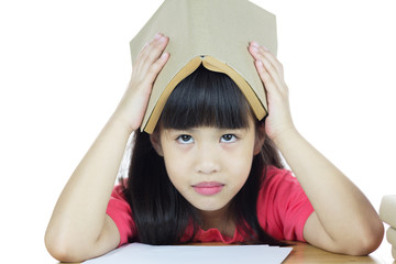 Serious school girl with book over head