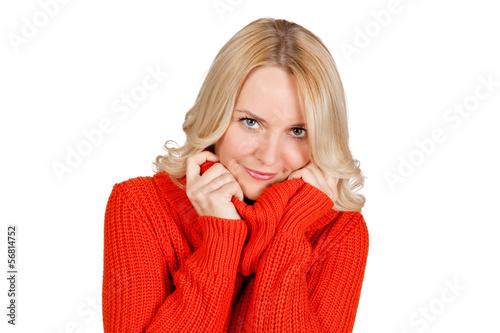 Attraktive blonde junge Frau kuschelt sich in ihren Pullover