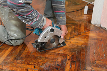 Home renovation worker cut old parquet floor with electric saw