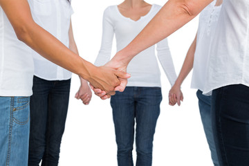 Women standing and holding hands in a circle