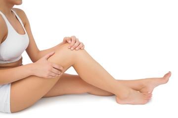 Slim woman sitting on floor touching her injured knee