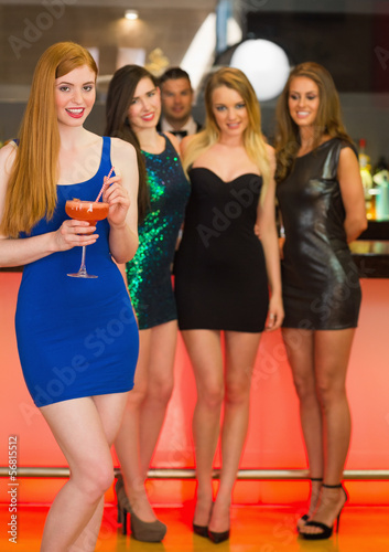 Beautiful woman standing in front of her friends holding cocktai