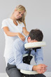 Masseuse treating clients neck in massage chair