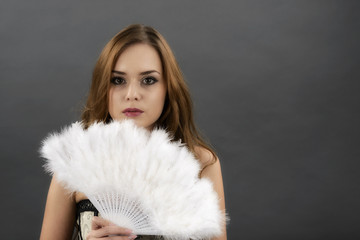 The young woman with a fan from gray  feathers