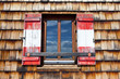 Wooden window with shutters in the national colors of Austria