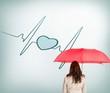 Businesswoman standing back to camera holding umbrella
