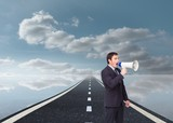 Standing businessman shouting through a megaphone
