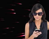 Concentrated brunette wearing sunglasses texting