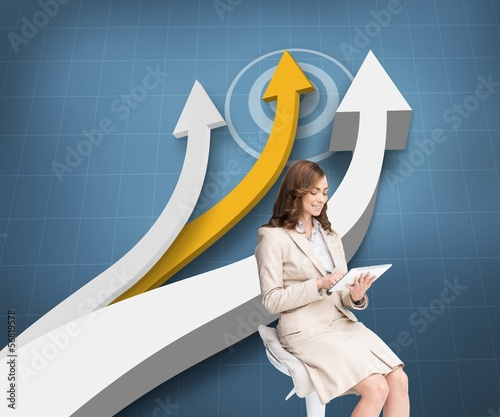 Pleased businesswoman using a tablet pc sitting on a bar chair