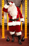 Sweating, tired Santa Claus having break in training in gym