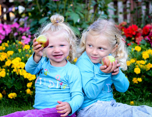 two blond girls holding an apple