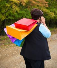 Woman talking on the phone and holding shopping bags