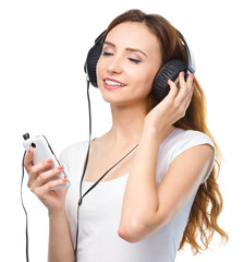 Young woman enjoying music using headphones